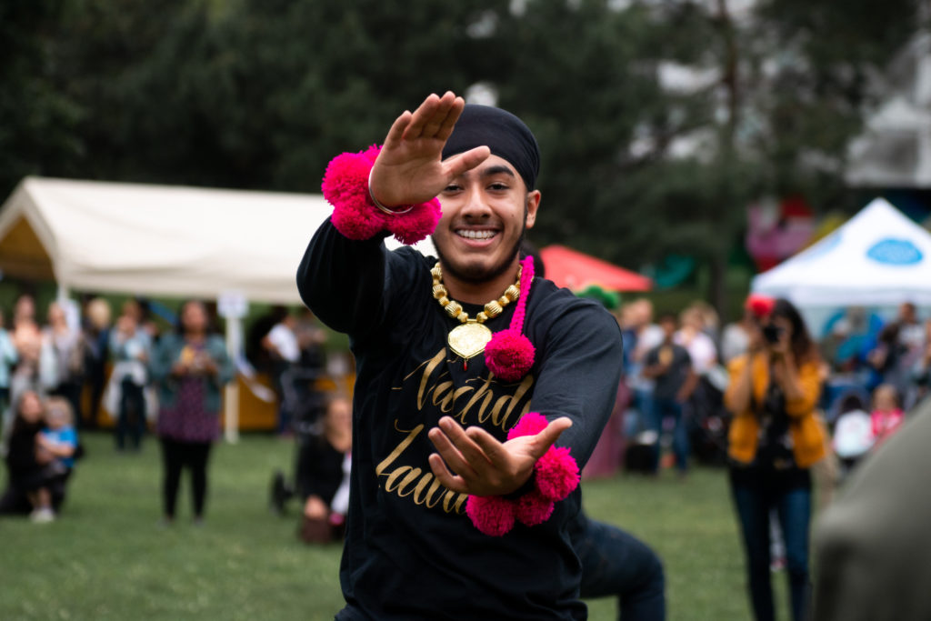 Dancer from Bhangra Troupe Nachdi Jawani smiling with arms outstretched to the camera. He is in all black with bright pink pom poms around wrists and neck.