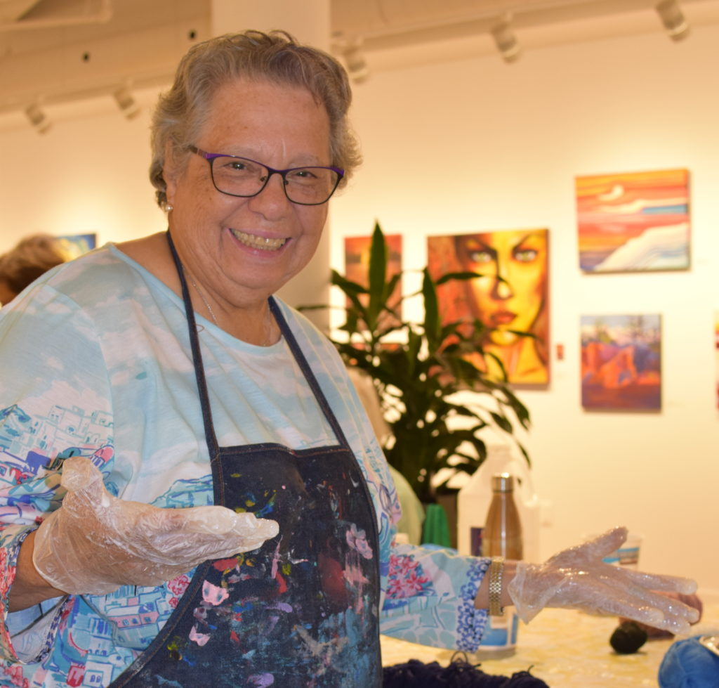 Close up of participant from our Seniors' Art Class smiling and showing her messy hands.