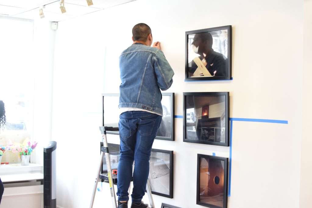 Man on a ladder installing photographs on a white gallery wall