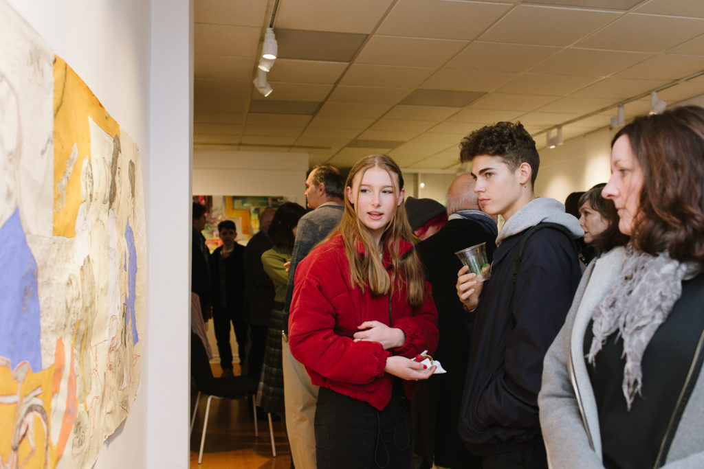 Three young people are looking at artwork on teh wall in the Arts Etobicoke Gallery