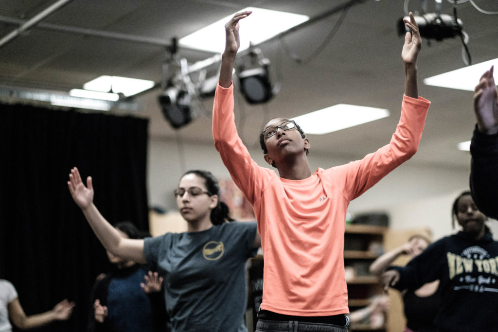 Teenagers holding a pose with arms upraised in a dance class.