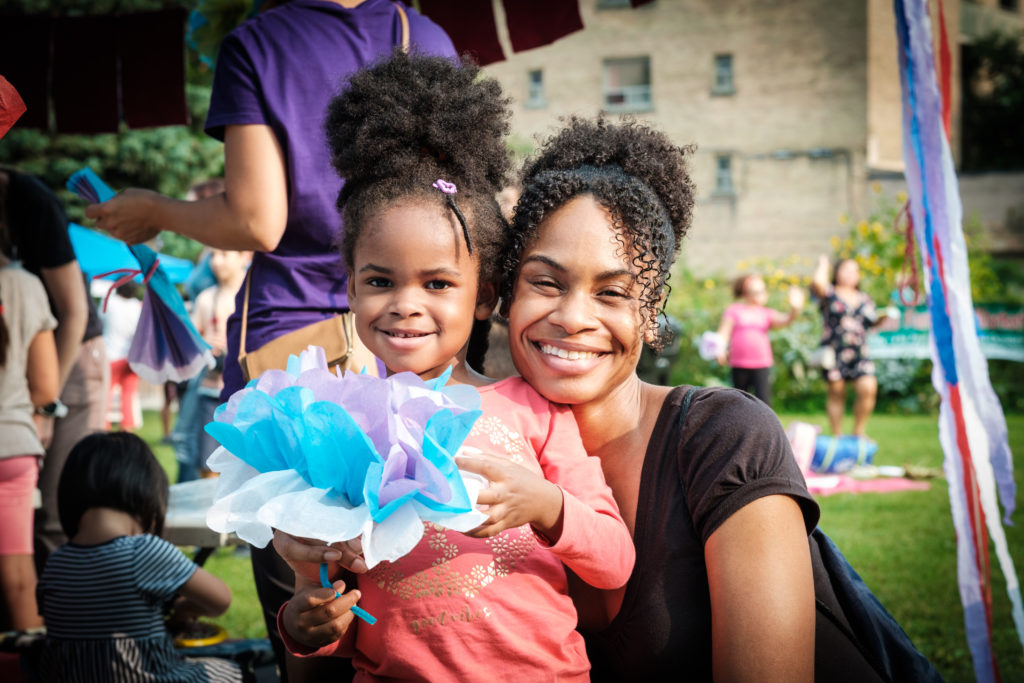 Close up of mother and daughter at our outdoor Park Party. Daughter is holding a crafted flower she made.