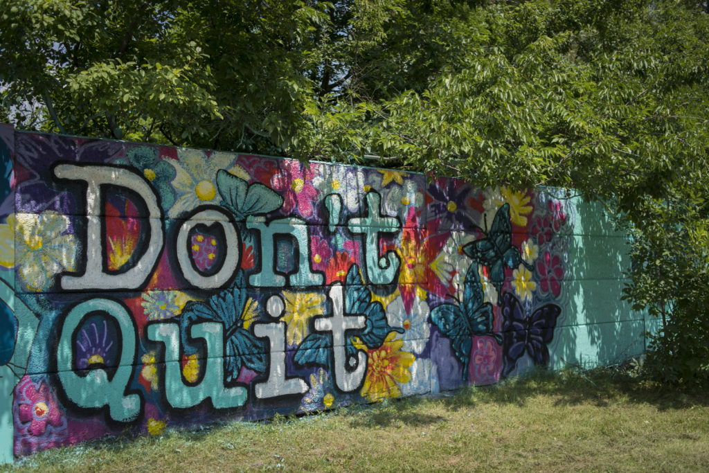 """Mural of floral design surrounded by tree branches with the words """"Don't Quit"""" large in the forefront of the design"""