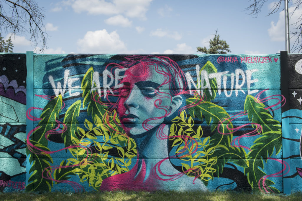 """Mural of aa oman's face surrounded by foliage with the words """"We are Nature"""""""