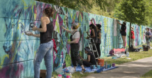 Line up women painting murals on a large wall